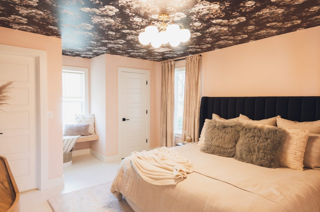 Light pink bedroom with window seat and dark, floral wallpaper on ceiling