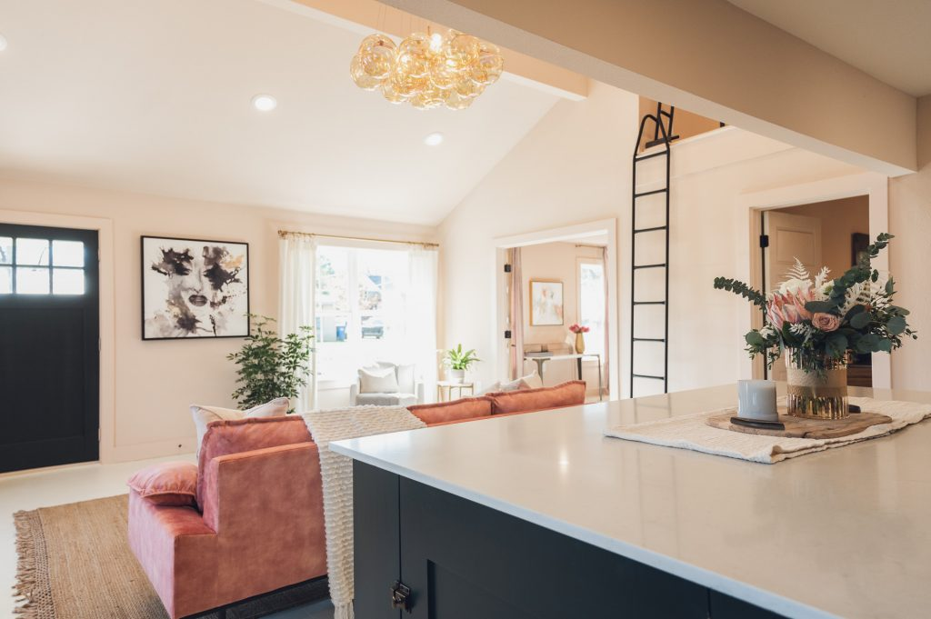 View from dark green kitchen island of remodeled living area with pink furniture
