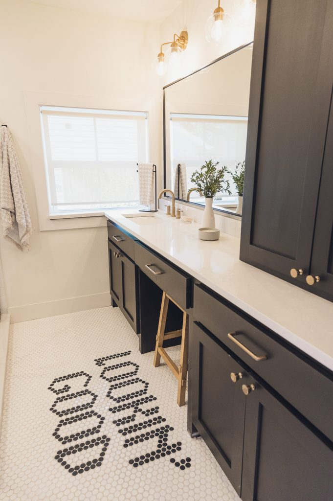 Bathroom with dark cabinetry, window, and penny tile