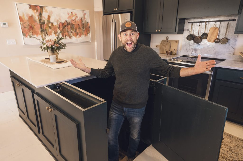 Dave Marrs revealing cellar space with pushed-back kitchen island