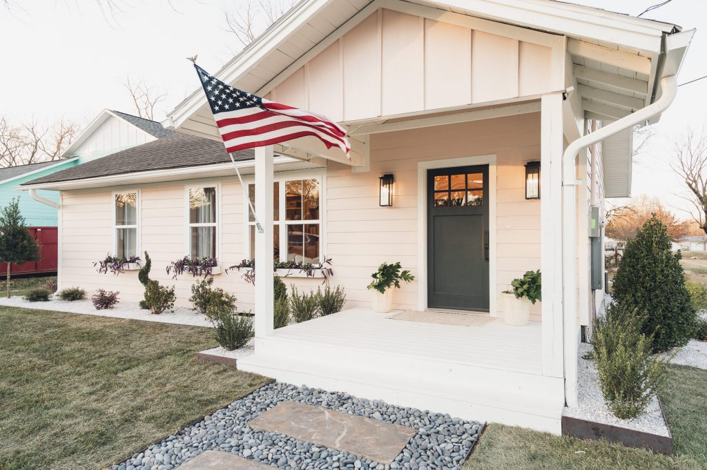 Light pink house with dark door and American flag on porch